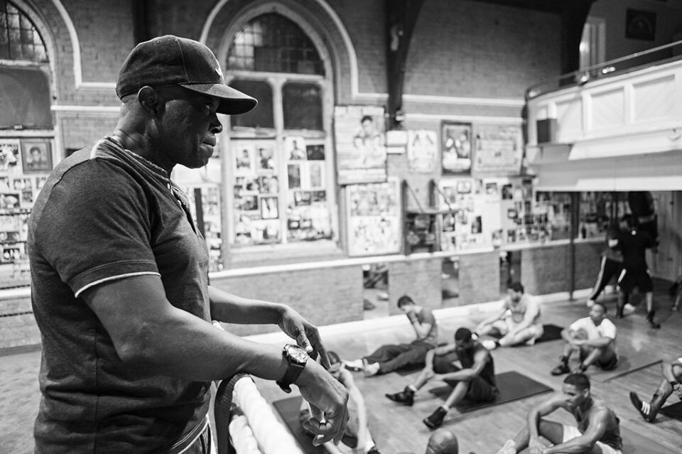 Mr Isola Akay (76 years of age) is overlooking the pupils doing exercises. Mr Akay comes to the club every day and spends all the time helping young boxers.