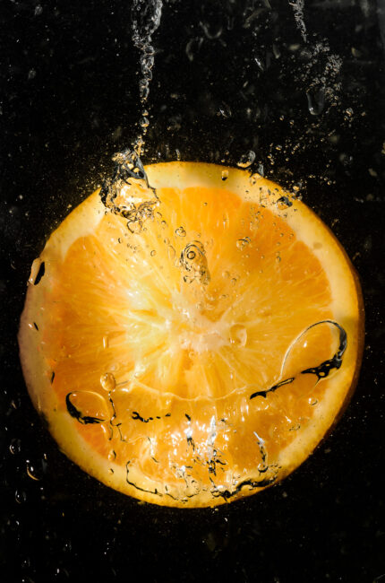 Orange slice falling into water with bubbles